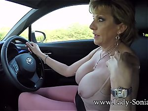 Mature gal Sonia plays with her fun bags while driving
