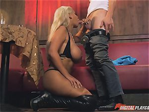 Bridgette B in super hot leather footwear and drills on a sofa